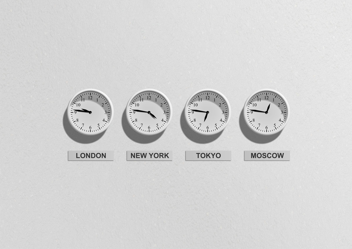 Image of four wall clocks showing different time zones around the world.