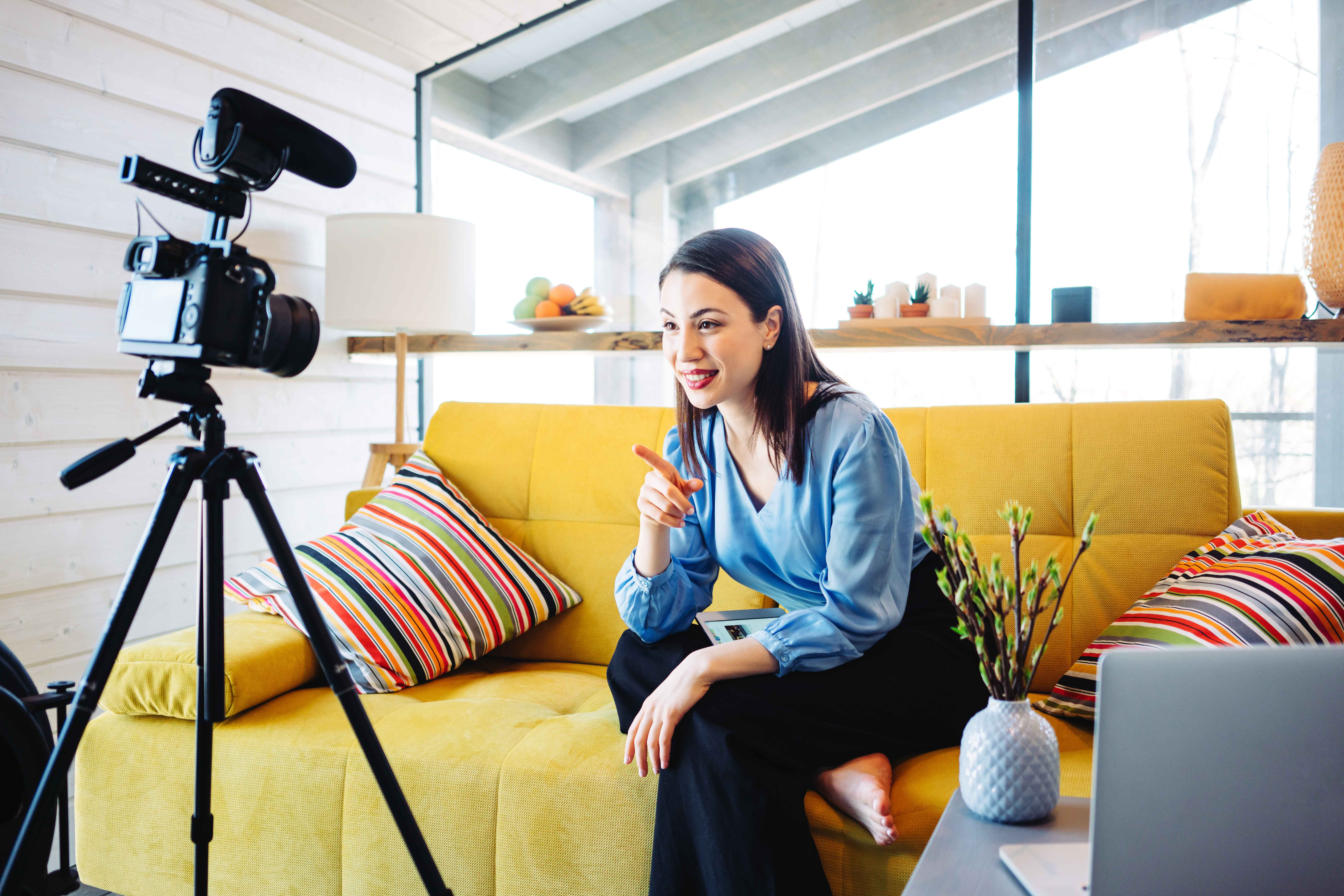 Woman seated on a yellow couch taping video content with a remote setup.