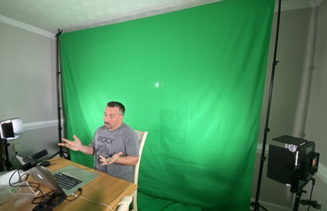 Man at a desk in front of a green screen, recording a presentation on a laptop.