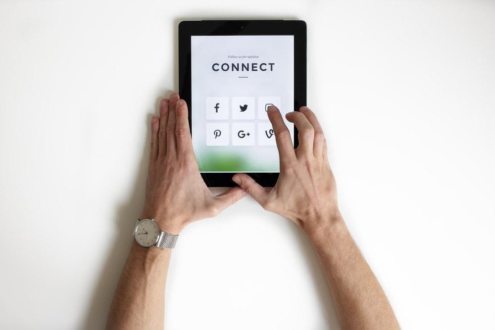 Male arms holding a tablet device showing connections to social media accounts.