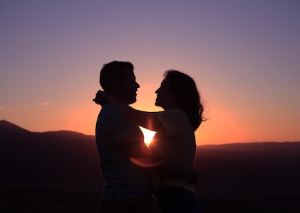 a man and woman couple embracing eachother with the sunset in the background