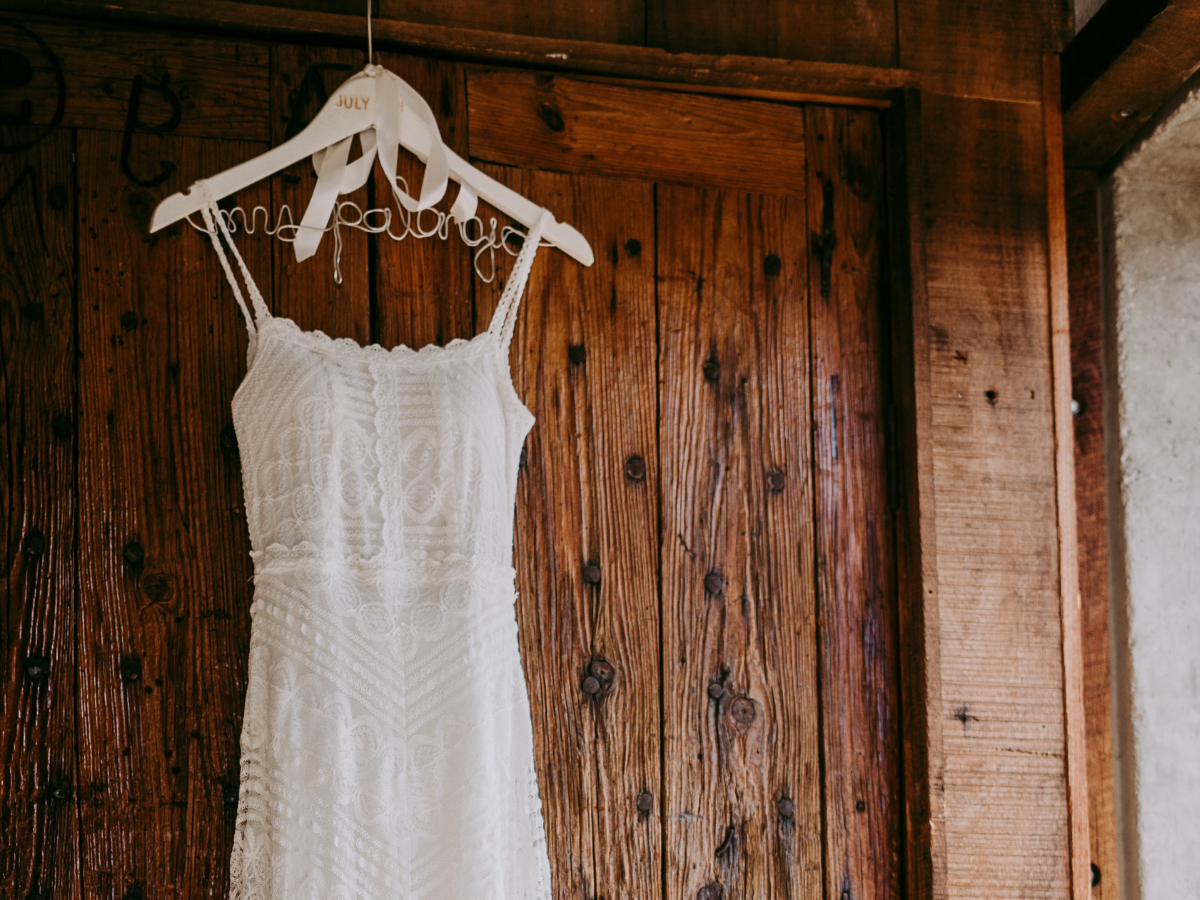 a wedding dress hanging on a door