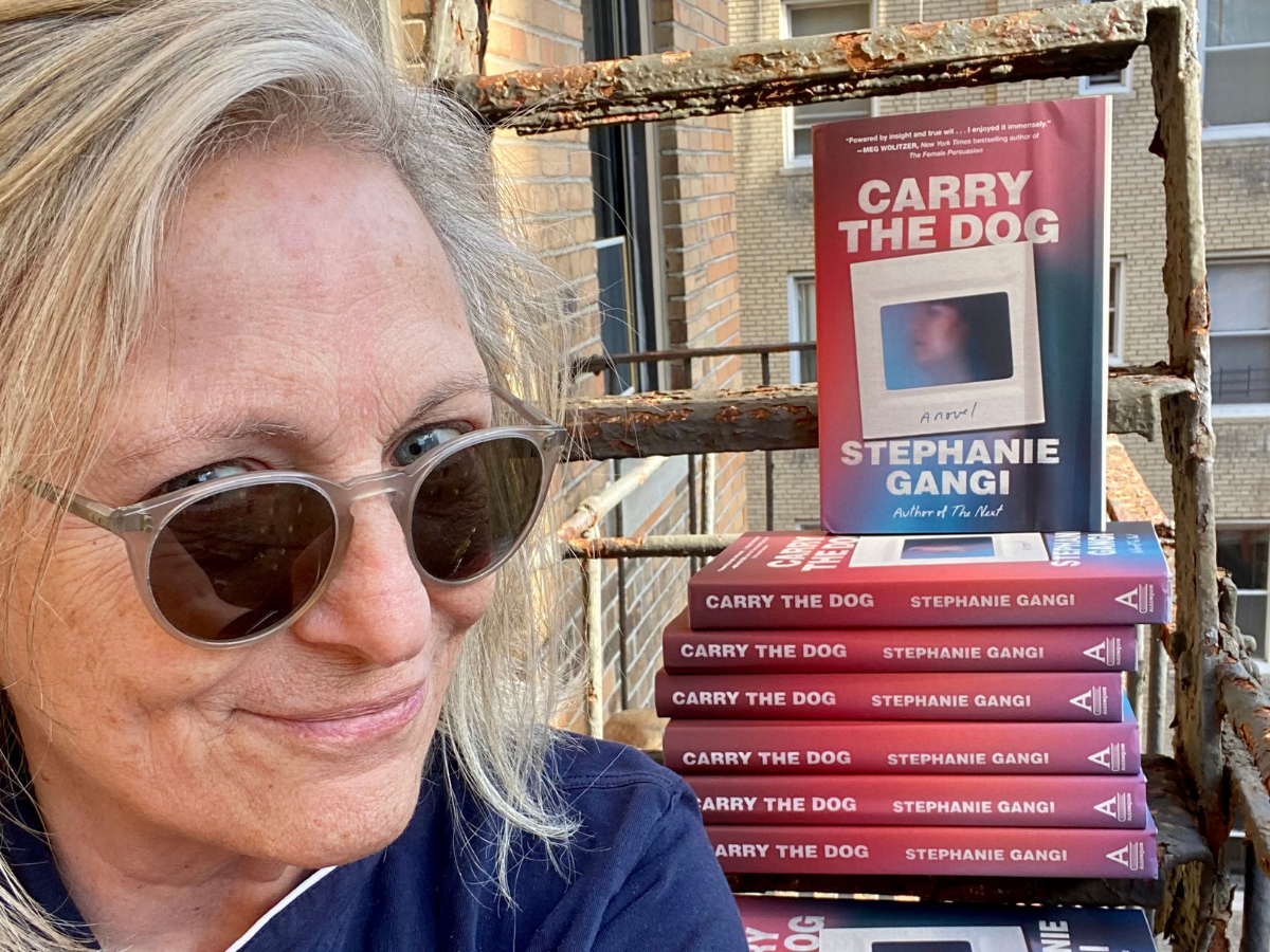 Stephanie Gangi in front of a pile of her book galleys.