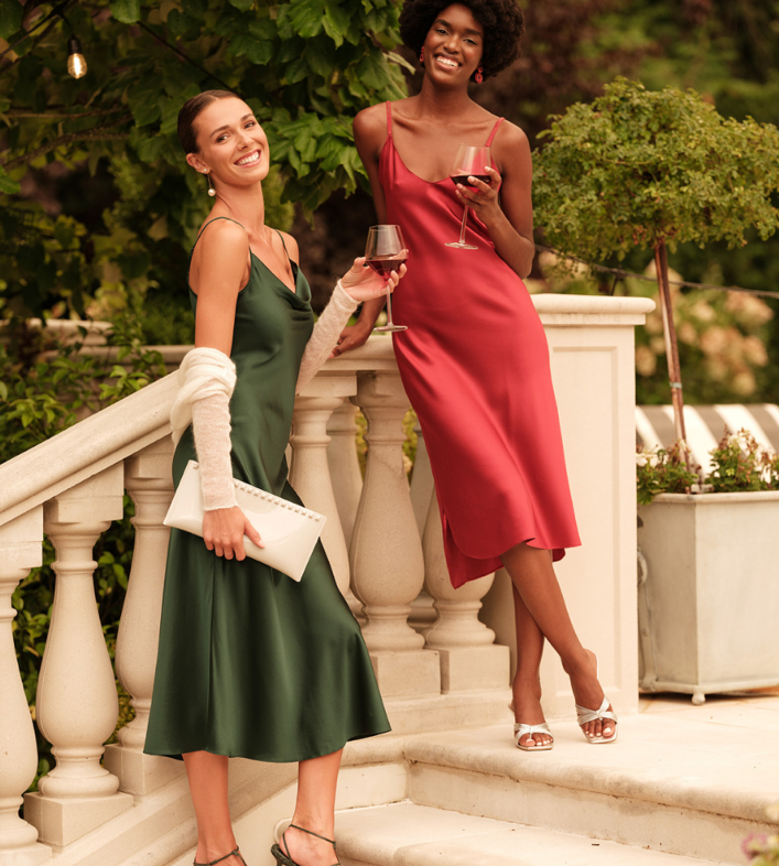 Two women in silk dresses holding wine