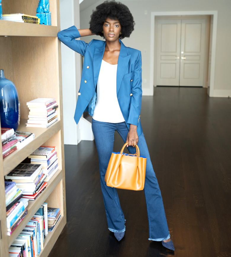 A woman in blue jeans and a blue blazer.