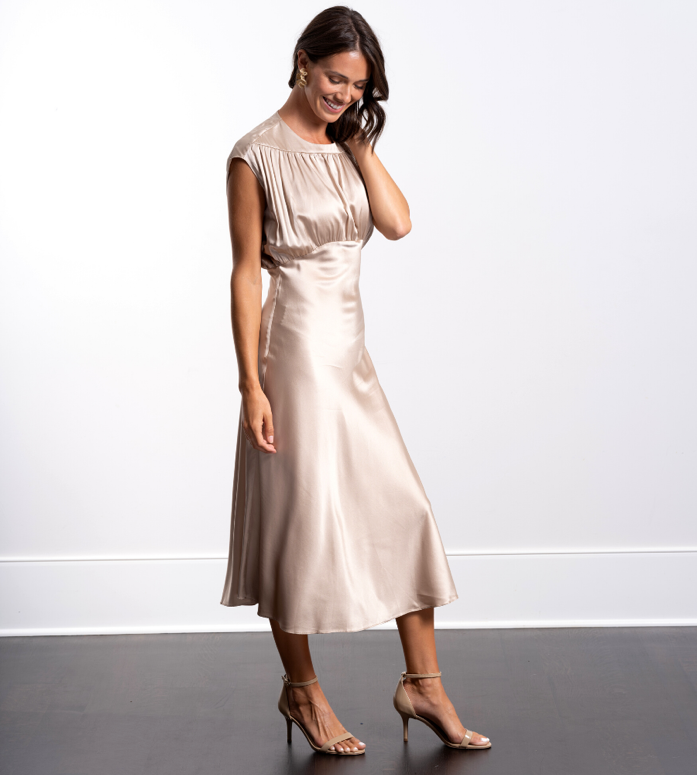 A woman in a silk dress and heels.