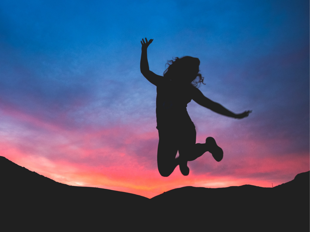 Woman jumps against a sunset background