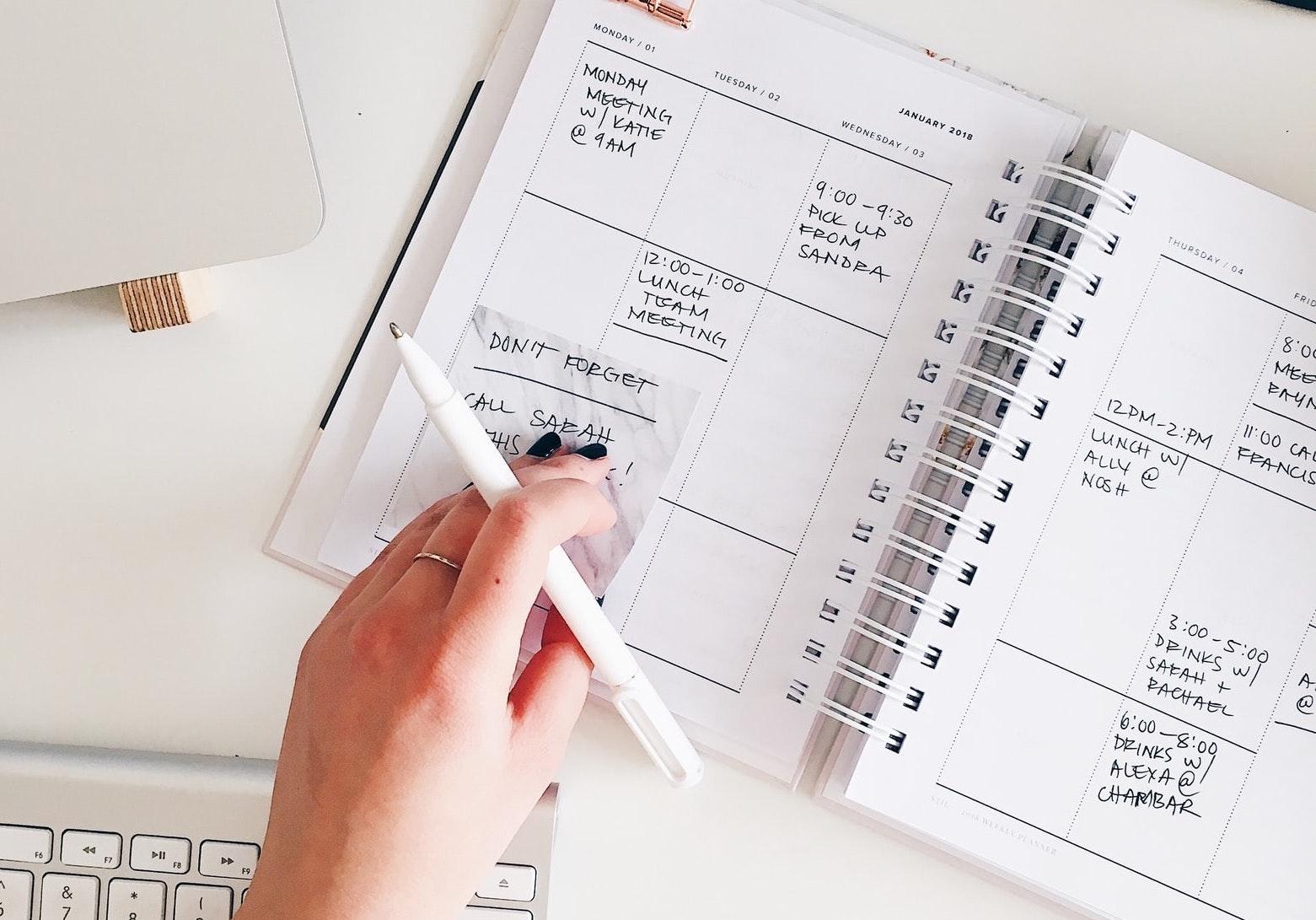 Hand adding reminder to calendar notebook