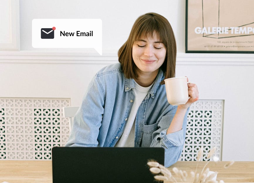 Smiling woman sitting in front of laptop receiving new email notification