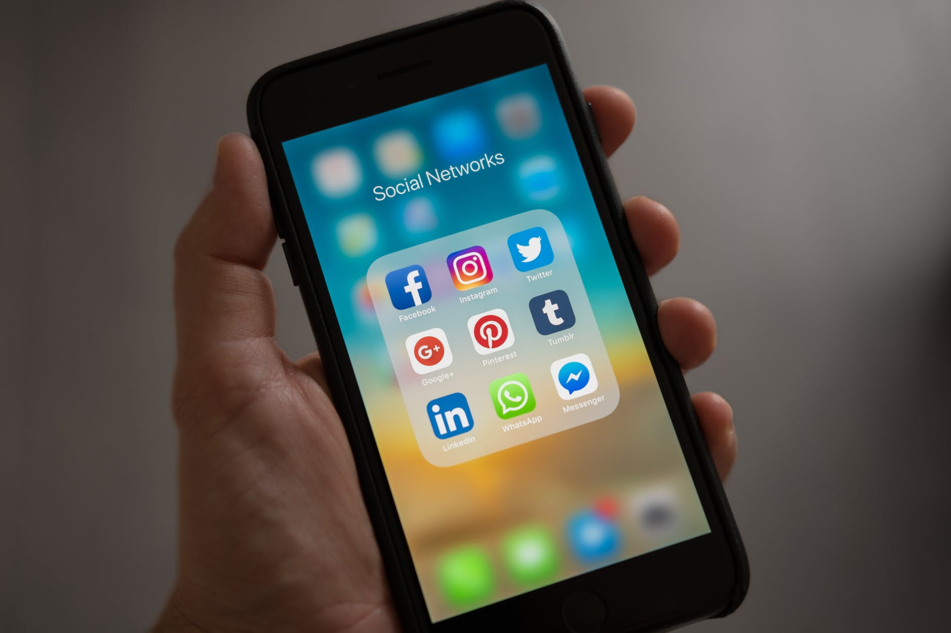 Phone showing social media apps in hand