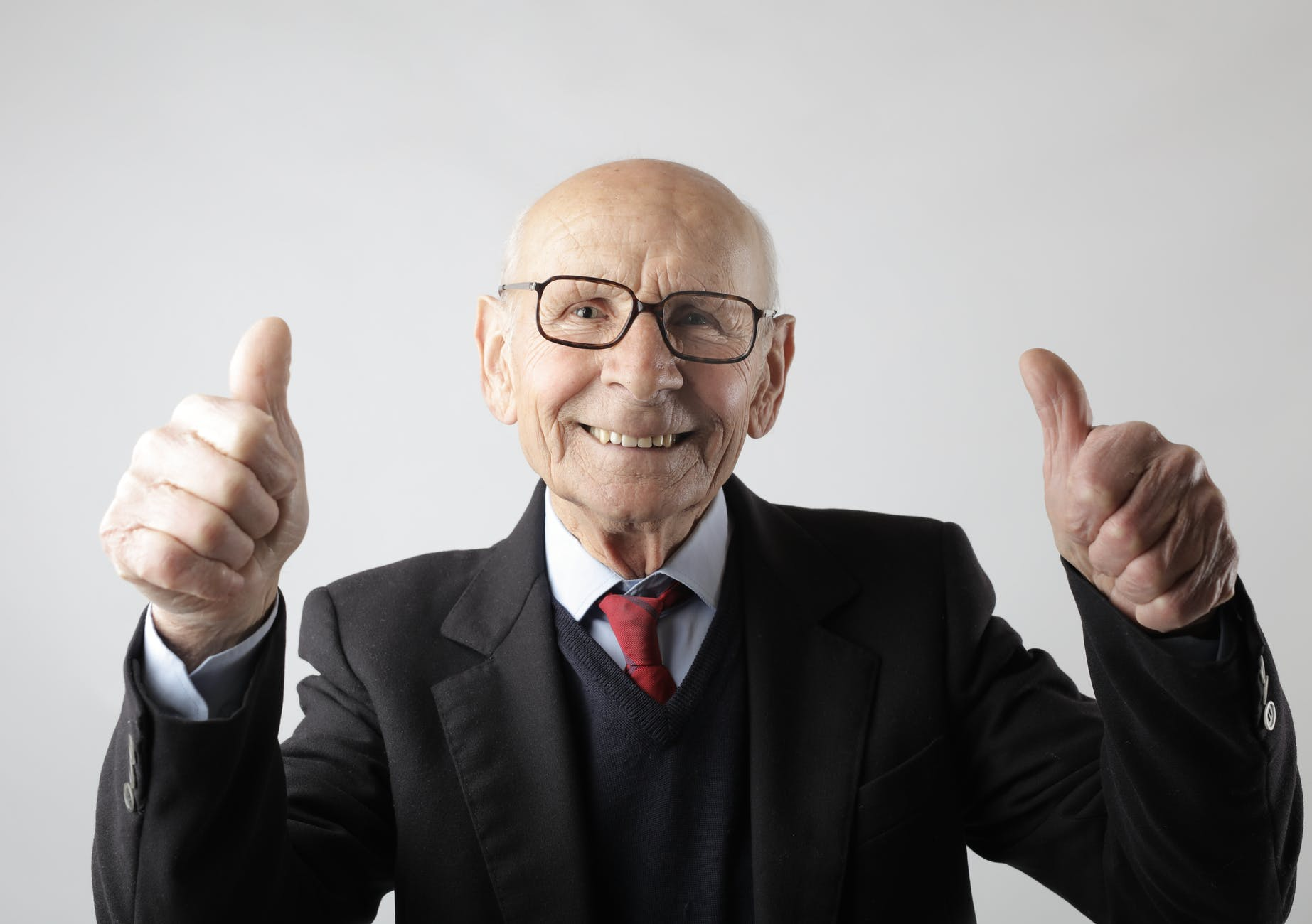 Elderly man giving a double thumbs up