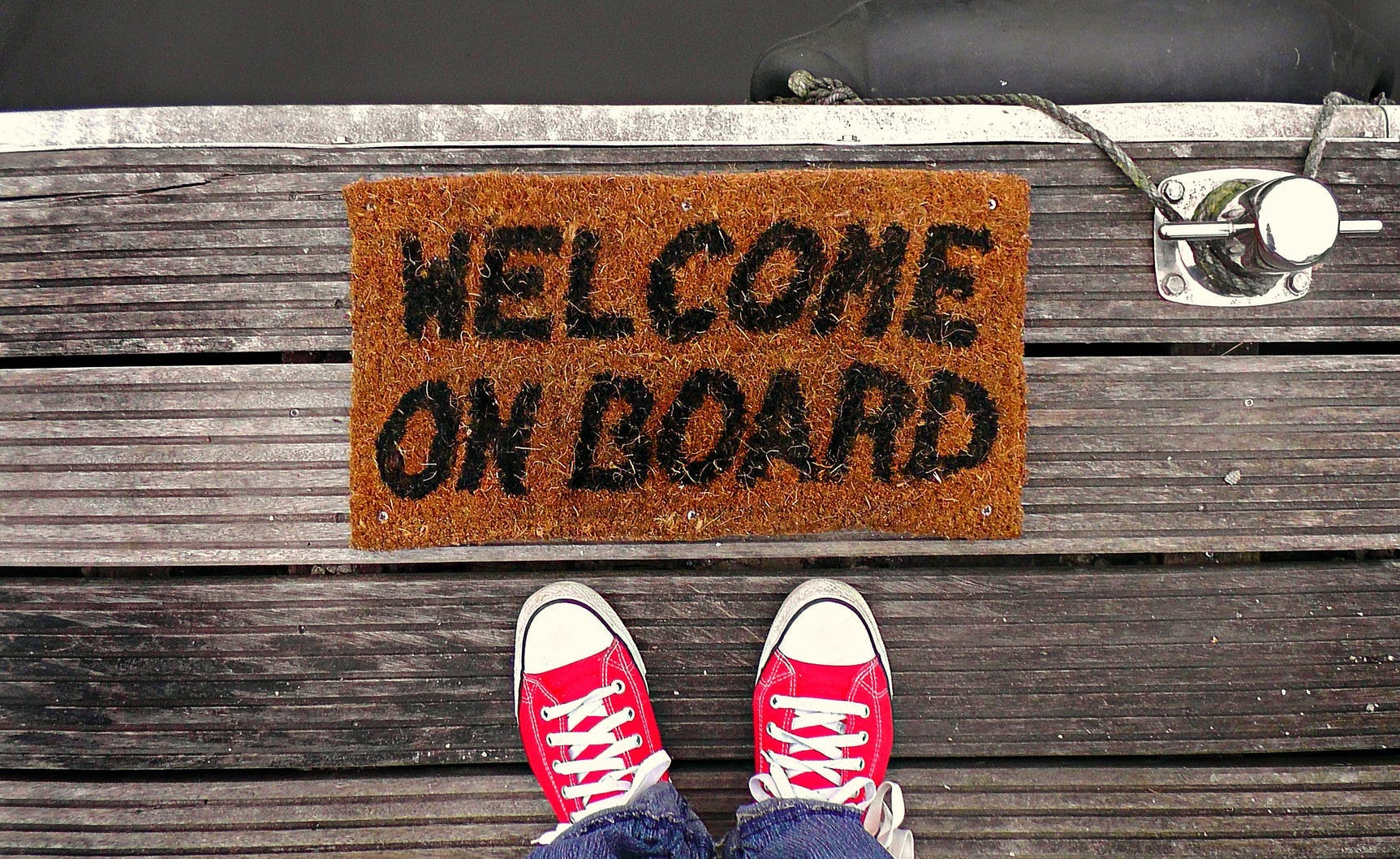 """Shoes next to """"Welcome On Board"""" mat"""