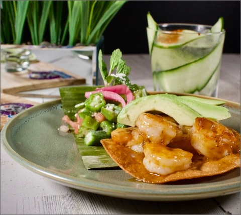 shrimp on a tortilla with a cocktail on a table