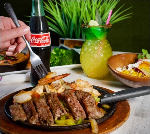 someone holding a shrimp on a fork by a plate of shrimp and steak fajitas with a Coca-Cola and pineapple cocktail in the background