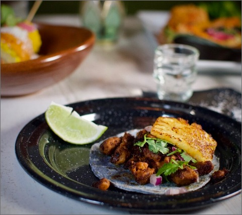 a Pastor taco with pork, grilled pineapple, onions and cilantro on a plate with a lime