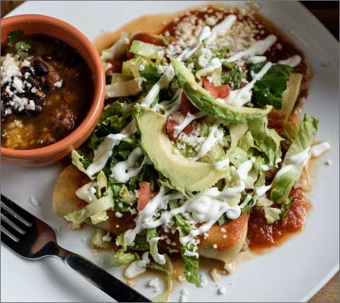 enchiladas with avocado on a plate and beans in a bowl