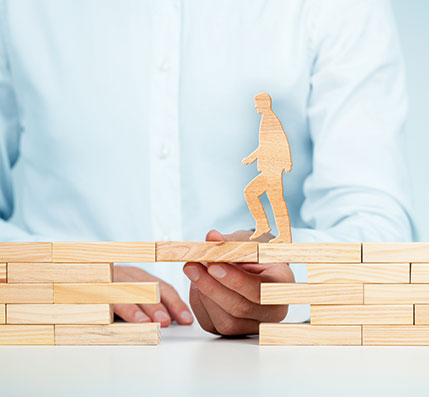 A wooden person crossing a wooden block held by a real hand.