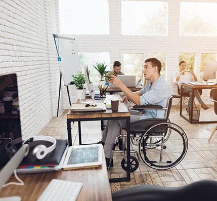 Man in wheelchair looking at his desktop.