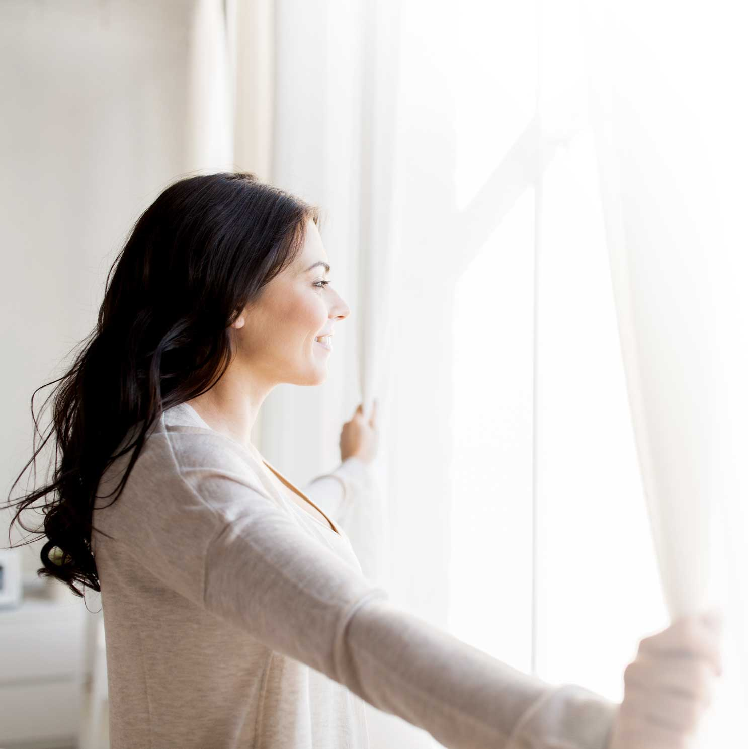Woman with long hair looking out of her window with both hands holding the curtains.