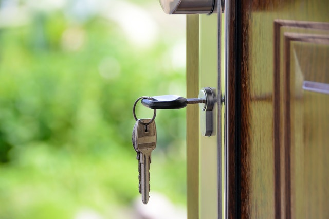 Door open with keys in it for a house that's for sale by a realtor