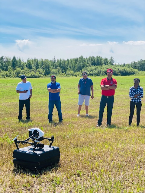 Five Manitoba Uske members at drone training in a field