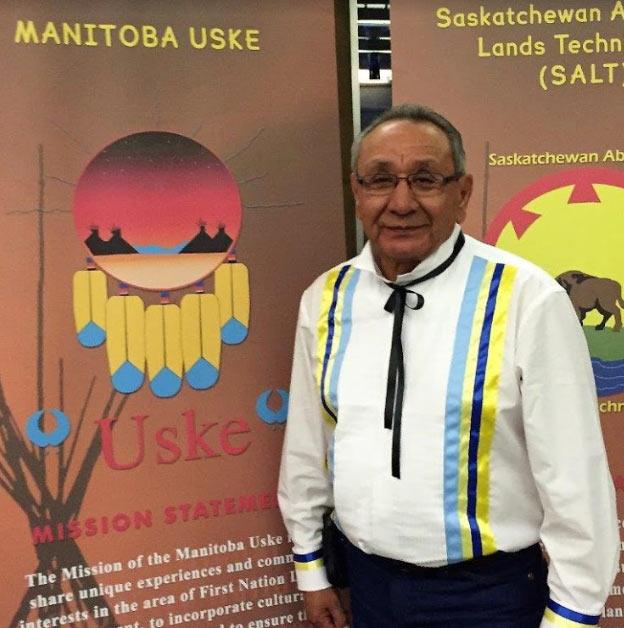 Manitoba Uske government relations, member standing in front of Uske banner