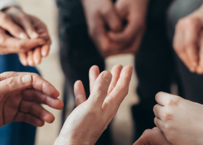 hands of people in a group therapy meeting