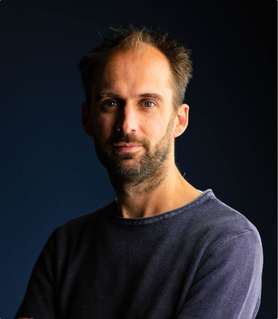 A man with a dark short beard smiling at the camera and wearing a blue and white striped t-shirt with a denim shirt on top