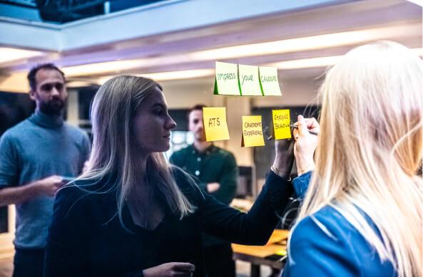 Schrijven op post its die aan het magneetbord zijn bevestigd met reflectie van de deelnemers op het bord.