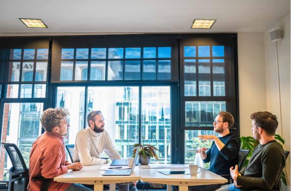 Deelnemers aan de HubSpot integratie workshop zitten aan een tafel te discussiëren.