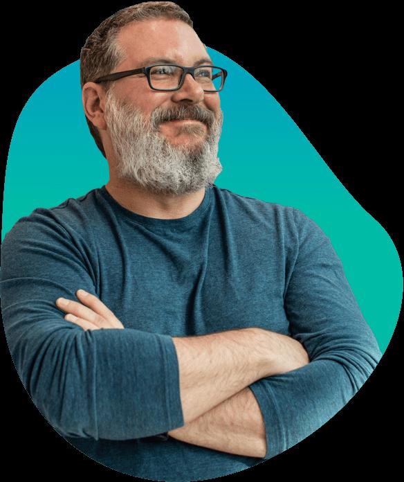 Een man met een witte baard en een zwarte rechthoekige bril en een groen t-shirt met lange mouwen vouwt zijn armen en glimlacht op een blauwe achtergrond.