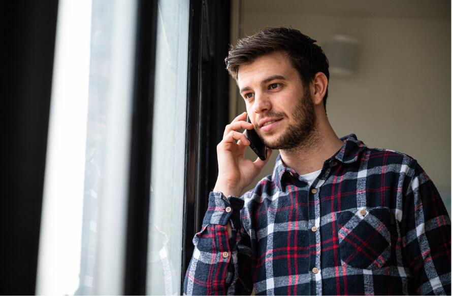 Sqales werknemer aan de telefoon met een tram en gebouwen op de achtergrond. Voorbereiding voor de verkooptraining.