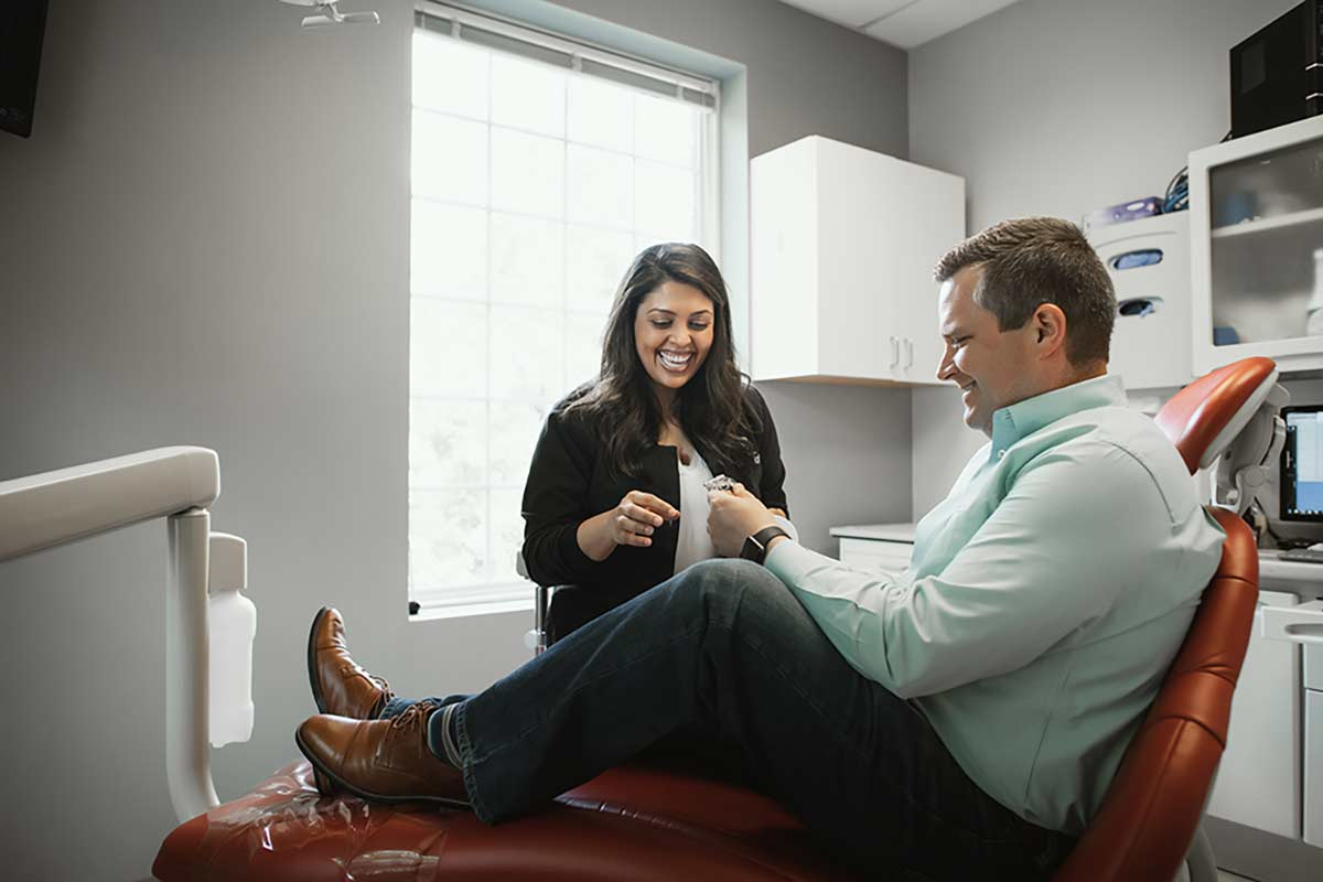 Photo of Dr. Patel showing a dental device to a patient who is sitting in a chair
