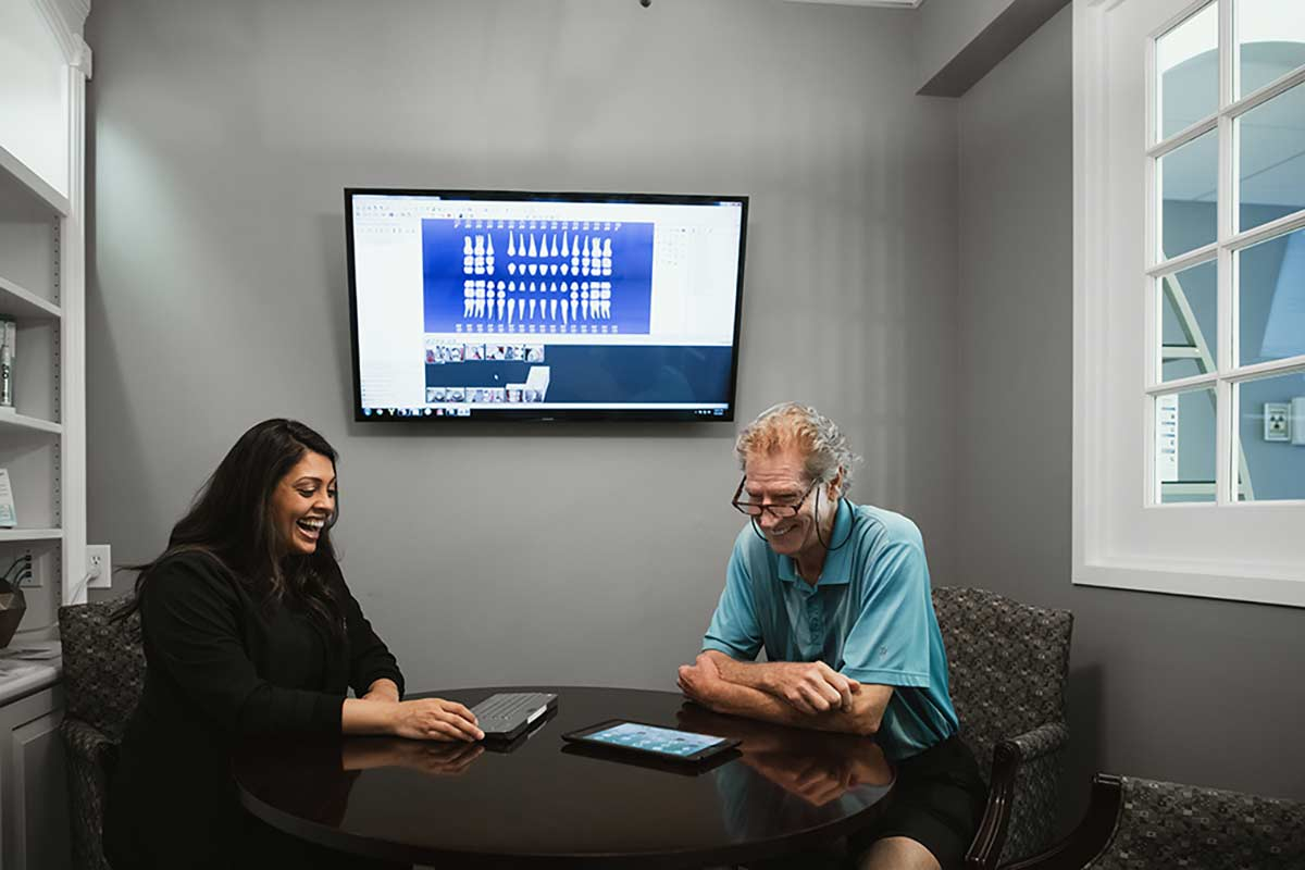Photo of Dr. Patel talking with a patient in the consultation room