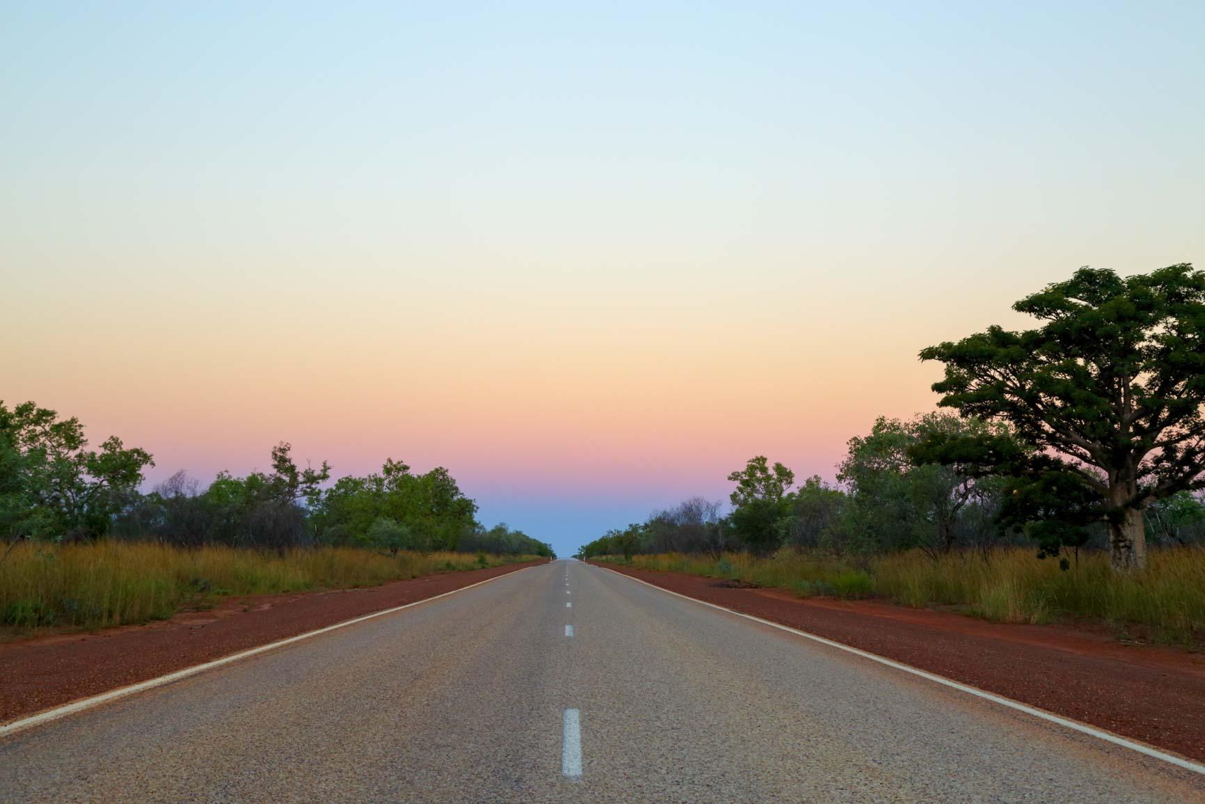 Long empty road cutting through Western Australian country side