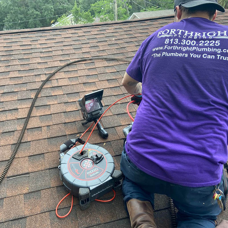 Owner of Forthright Plumbing on roof performing drain cleaning services in Tampa, FL