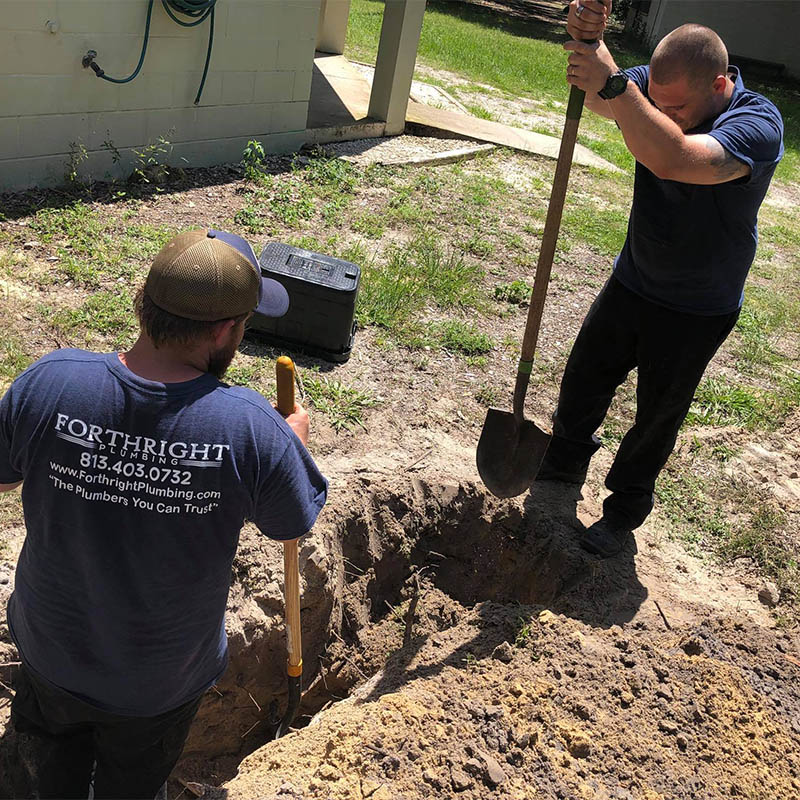 Forthright Plumbing employees digging hole to lay new pipe in Tampa, FL