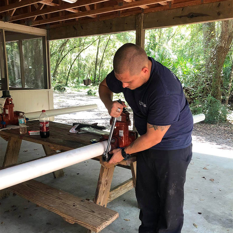Forthright Plumbing employee cutting PVC pipe in Tampa, FL