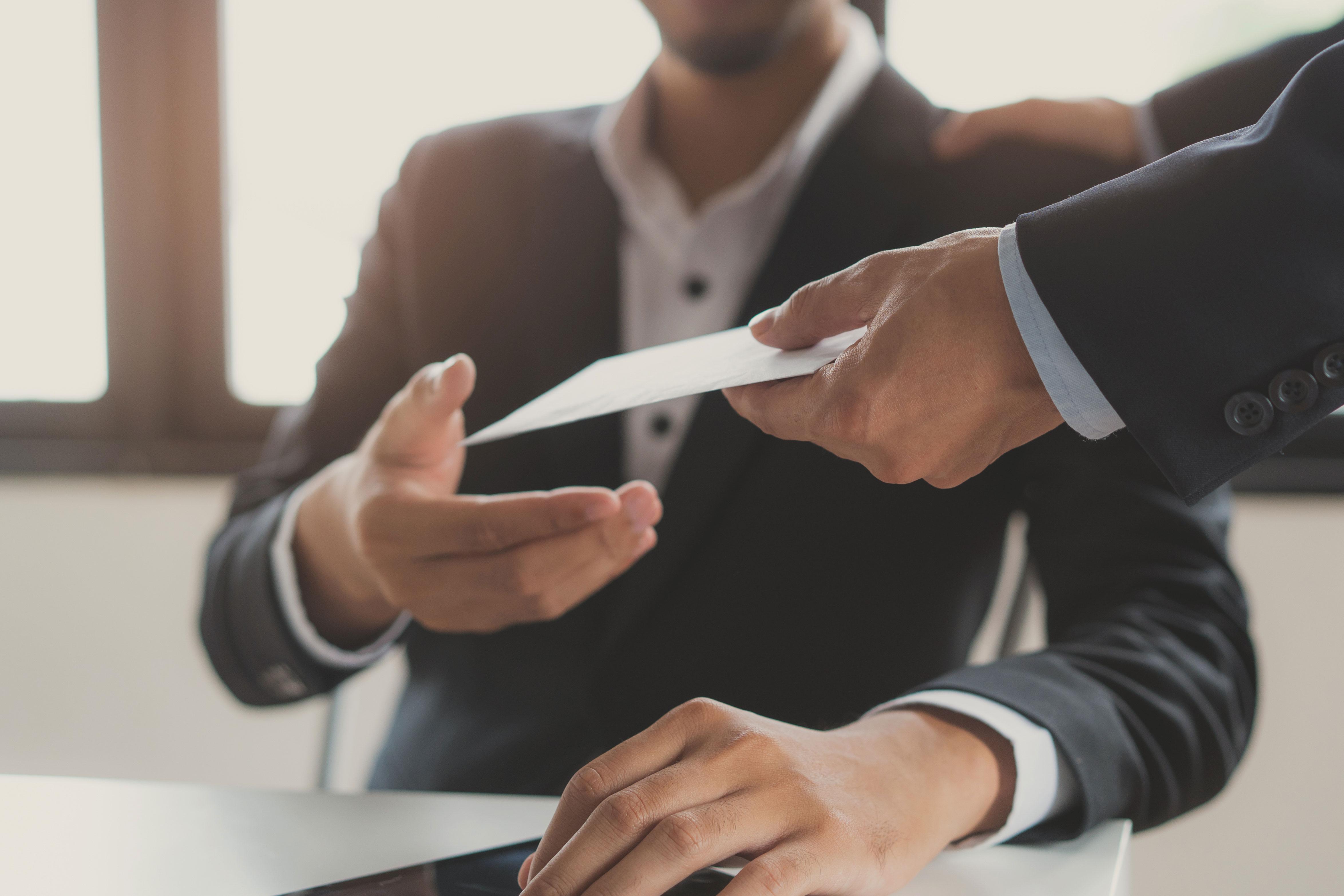 Man in a suit handing employee a reimbursement check