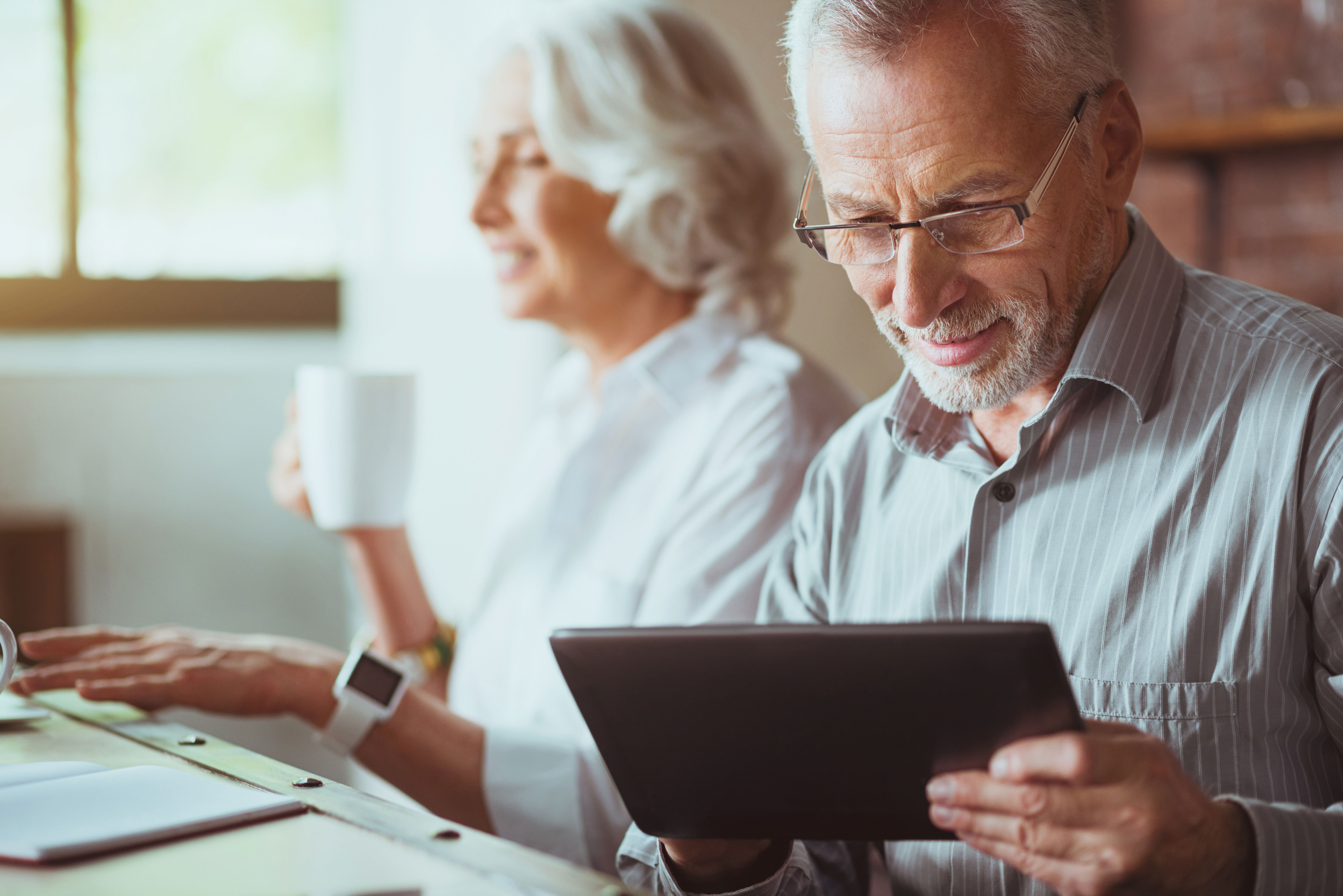 Senior couple drinking coffee and using a tablet device
