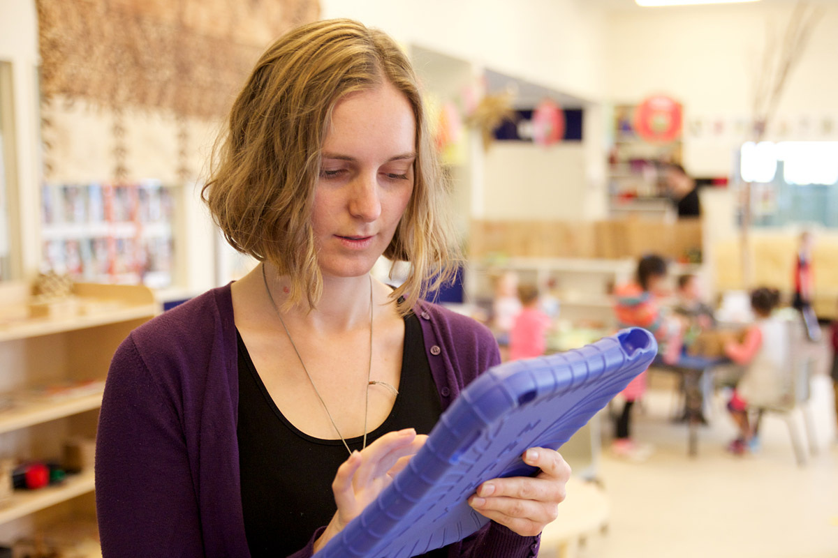 Female teacher holding a tablet device