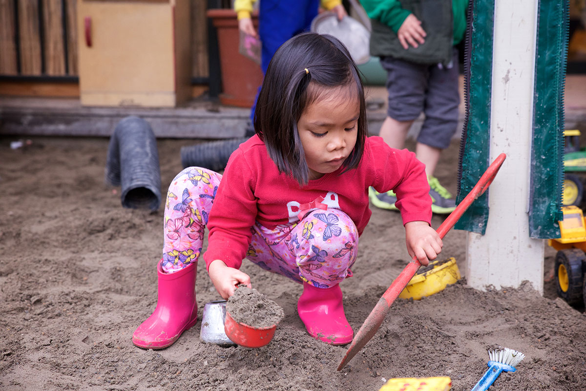 Toddler playing with mud outside
