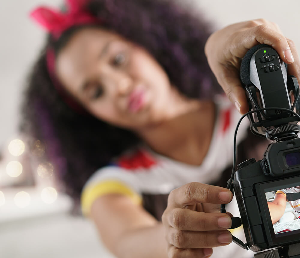 Social media influencer setting up DSLR camera for recording