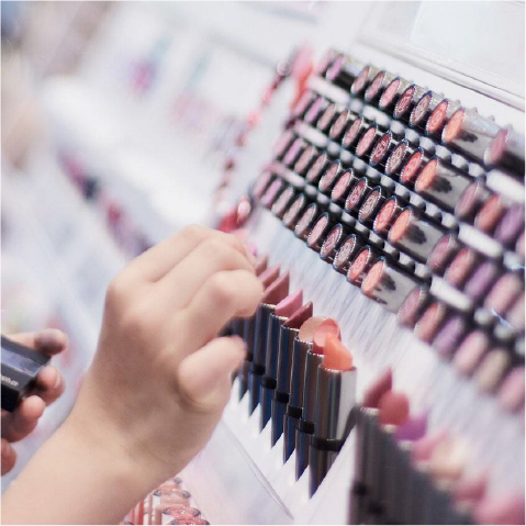 a hand reaching to select a tube of lipstick from a store shelf