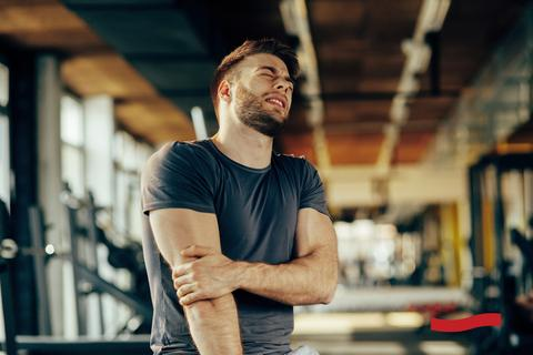 man with sore arm inside a gym