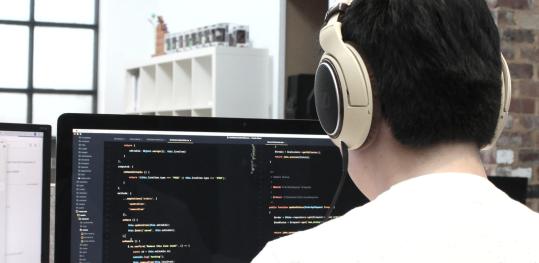 Person programmiert an einem Desktop PC