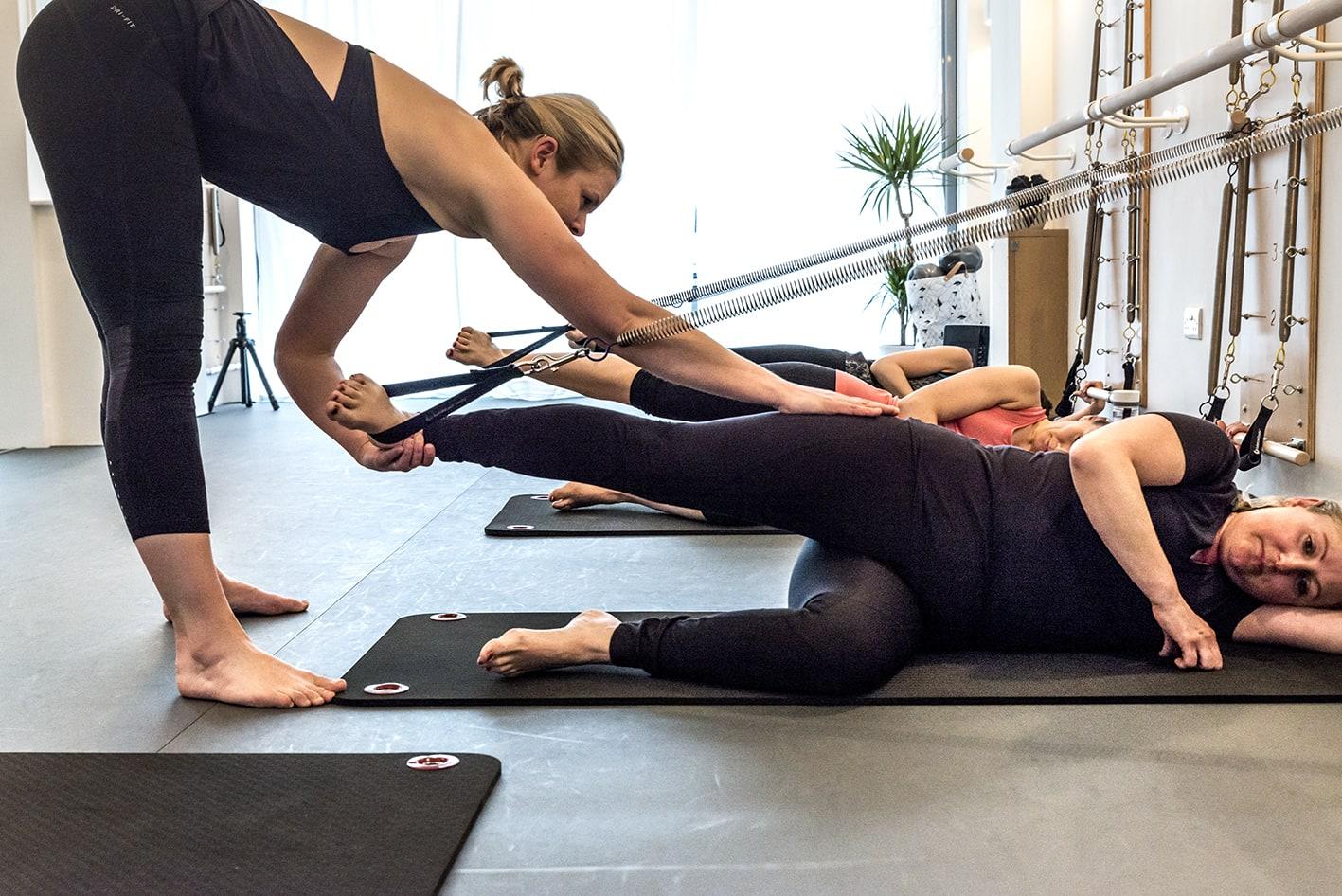 teacher adjusting pilates students