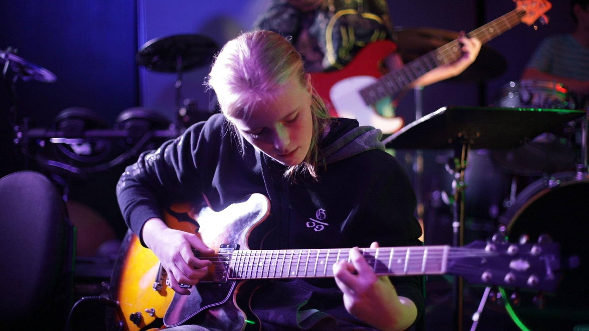 teenage girl playing an electric guitar