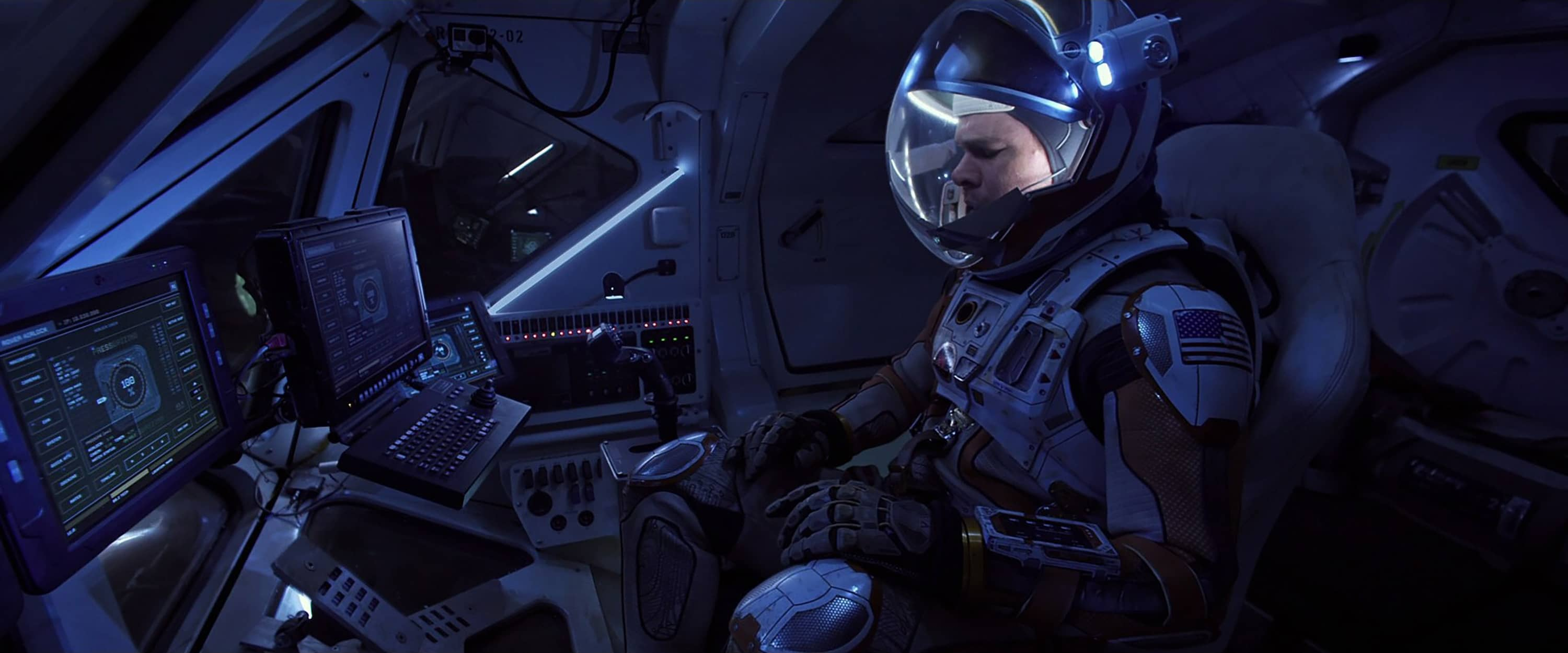 A man sitting inside the cockpit of a spaceship