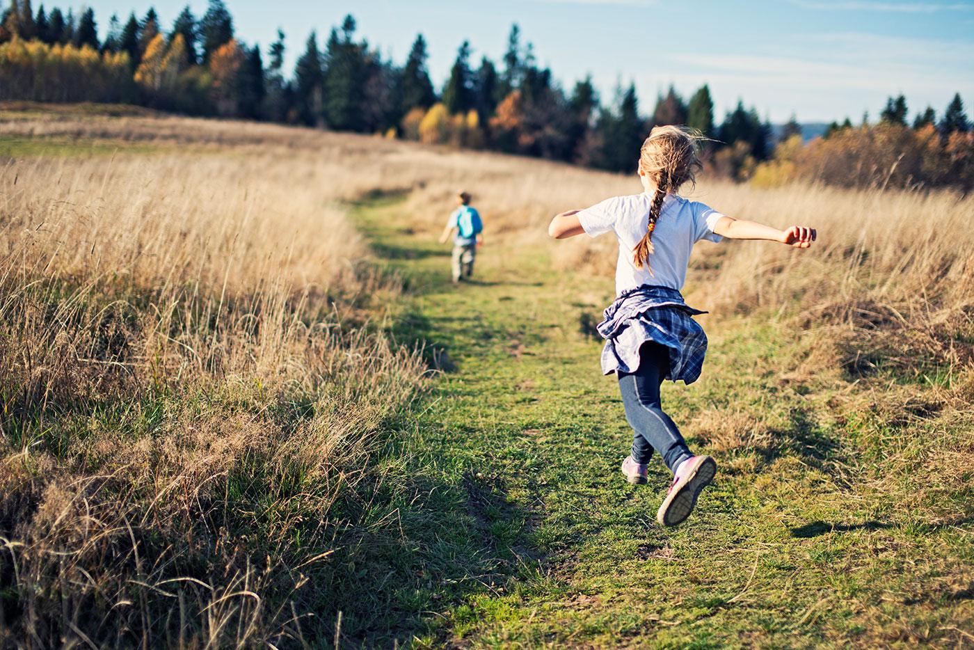 To børn løber om sommeren over en mark